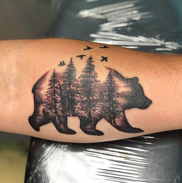 Grizzly bear with a forest inside tattoo by @shaina.chavda