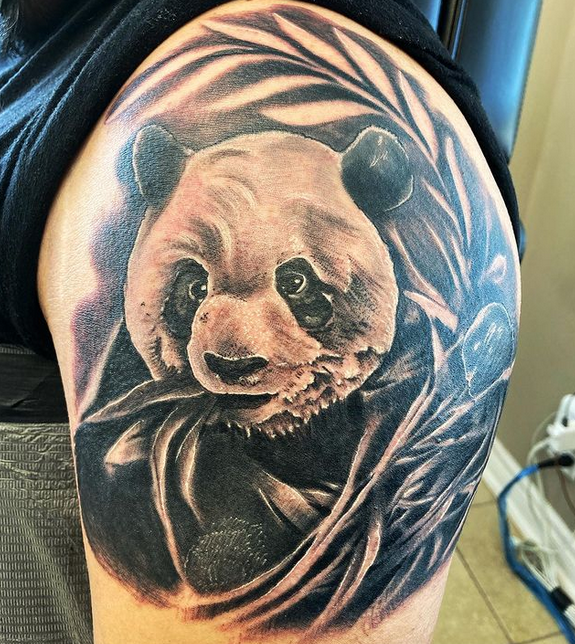 Realistic panda eating bamboo tattoo by @rui_tattoo