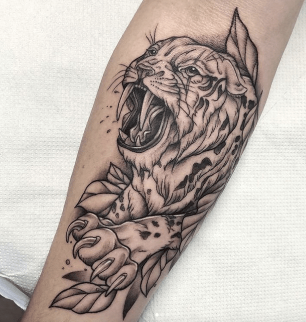 Leaves behind saber tooth tattoo by @amyorchard_tattoos