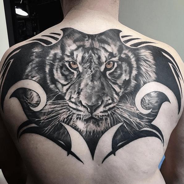 Realistic tiger on tribal background tattoo by @jodyknight_tattoo