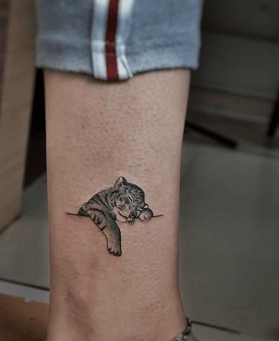 Small baby tiger tattoo sleeping by @bhagyesh_inksane_tattoo