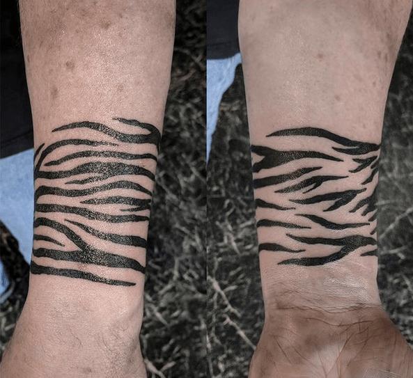 Small tiger stripes band tattoo by @adamharmontattoo