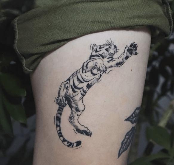 Tiger cub playing tattoo by @transcendance.tattoo