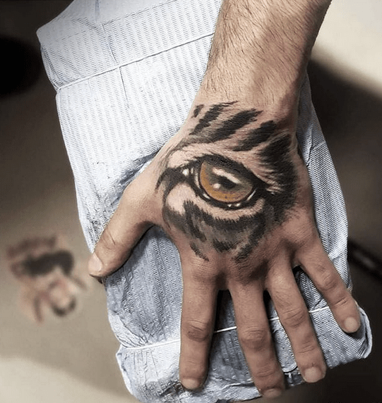 Tiger eye on the hand tattoo by @guylevintattoo