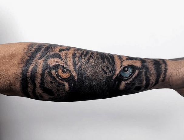 Tiger eyes tattoo brown and blue by @kumaratattoostudio
