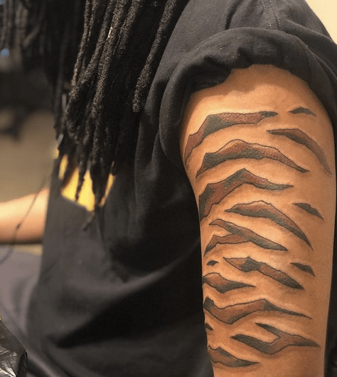 Tiger stripes on the upper arm tattoo by @sirreddent