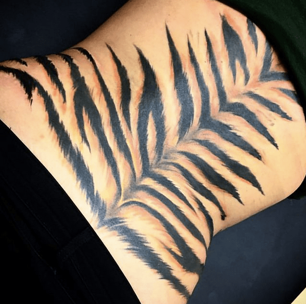 Tiger strips on the back tattoo by @treble.art.studio