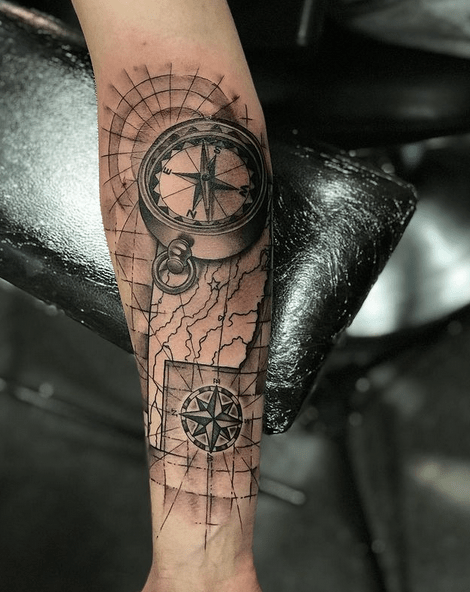 Black and white compass and map tattoo on forearm by @studio21tattoo
