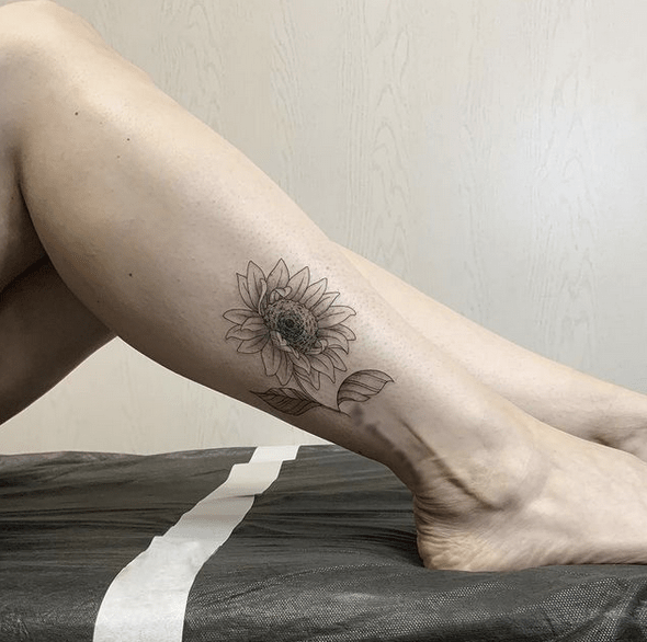 Black sunflower on the ankle tattoo by @sashafilink