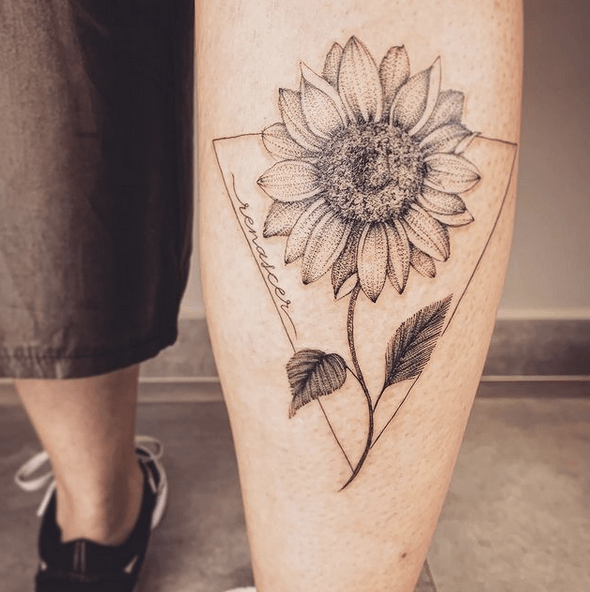 Dotwork sunflower in a triangle tattoo by @marte.art
