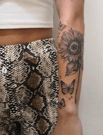 Forearm black butterflies and sunflower tattoo by @pattgonzalezart_