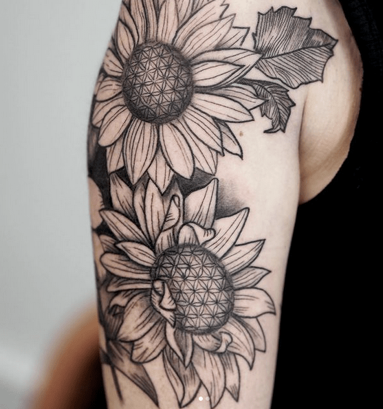 Shoulder two black sunflower tattoo by @stevi.ink.atelier