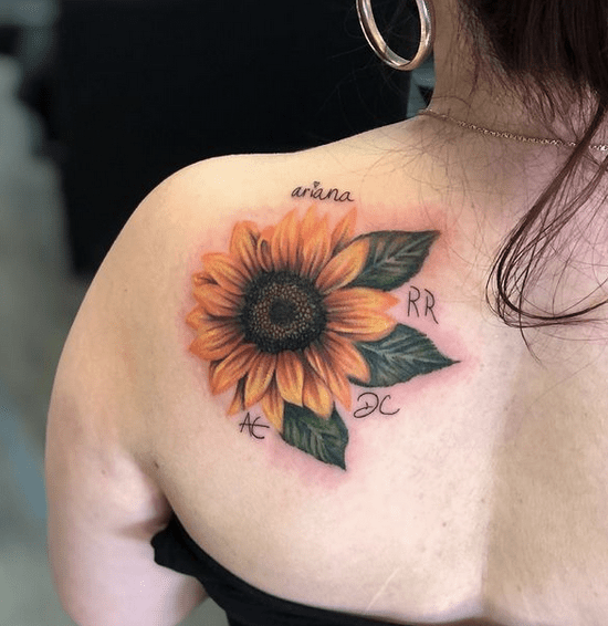 Small sunflower head tattoo with names by @ska.nelly