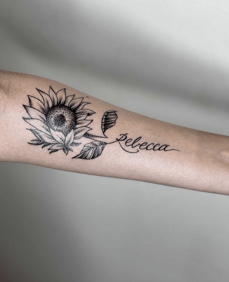 Sunflower with a name in the stem tattoo by @danielsosotattoos