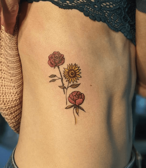 Two roses and a sunflower rib tattoo by @strange.mukai