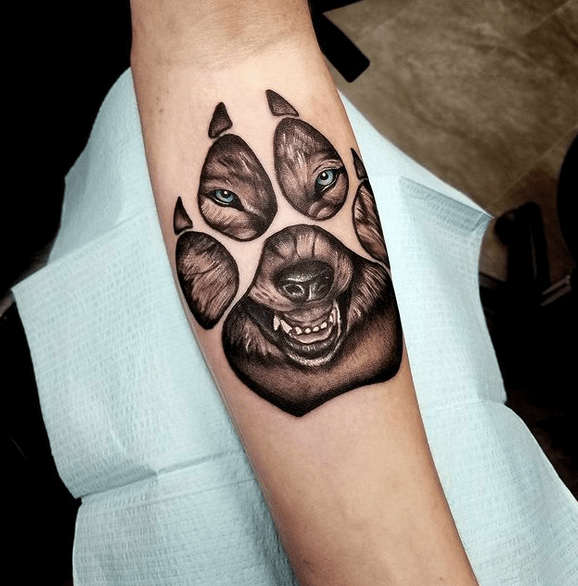 Angry wolf in a paw tattoo by @jkennon_tattoos