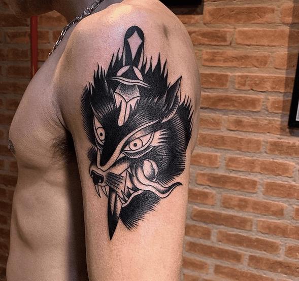 Black traditional wolf head dagger tattoo by @danilomatsubara