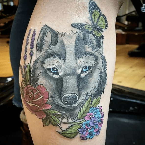 Feminine wolf head tattoo with flowers by @evermore_gallery