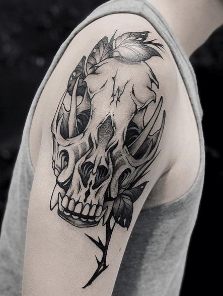 Shoulder wolf skull tattoo with leaves by @blackalchemystudio