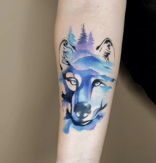 Small blue watercolor wolf tattoo by @alev.sari