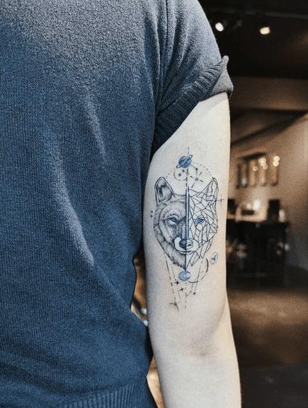 Small geometric wolf head tattoo by @hannah.tattoos