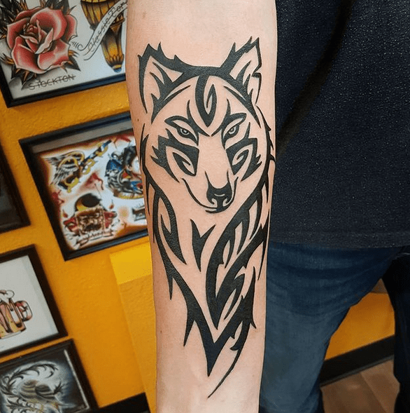 Sophisticated tribal wolf tattoo by @thepiratesloungetattooparlor