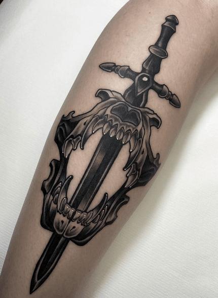Wolf skull dagger tattoo by @zmoratattoo