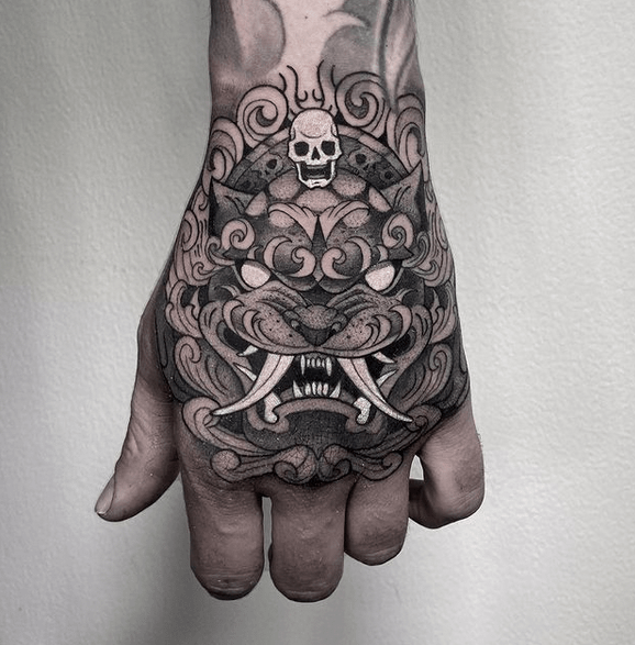 Black and white fu lion tattoo on the hand by @petitemortattoo