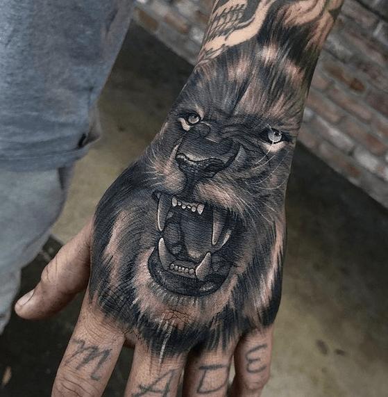 Black roaring lion hand tattoo by @bakon_one