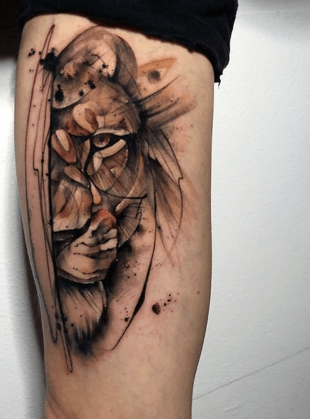 Brown watercolor lion tattoo by @shuster.tattooer