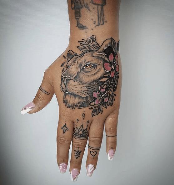 Lioness and flowers hand tattoo by @sacredskinstudio