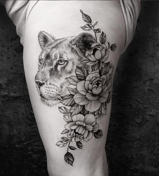 Realistic female lion with peonies tattoo by @bartek.pochowski