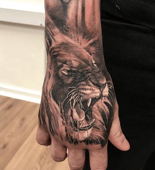 Roaring lion hand tattoo by @brothersinartstattoo