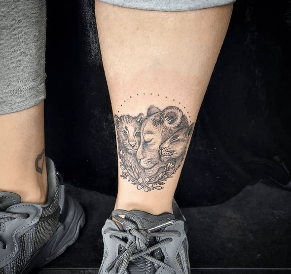 Small ankle lion and cub tattoo by @katiemaytattoo