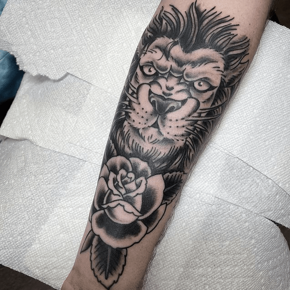 Traditional lion and rose tattoo by @nick.k.tattoos