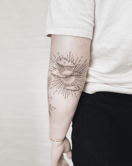 Upper arm clouds and sun rays by @ jackomotattoo