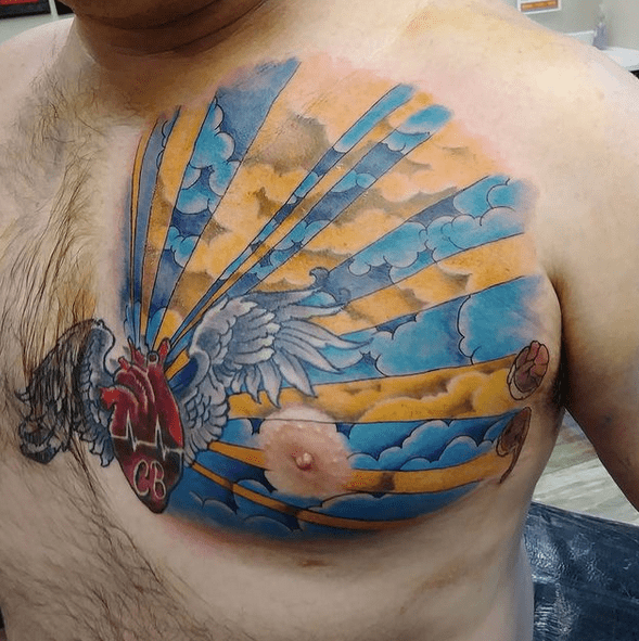 Colorful sun rays around the heart by @armand_p_tattooer
