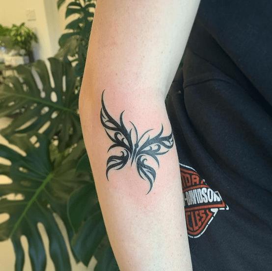 Small tribal butterfly tattoo by @elliott.tattoo