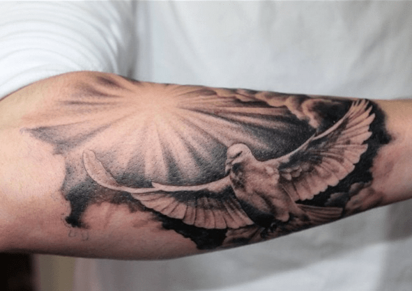 Sun rays and a dove tattoo by @truetattoolondon