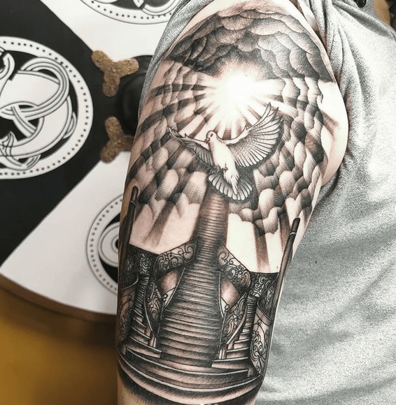 Upper sleeve sun rays tattoo with clouds and a dove by @deannorthtattoos